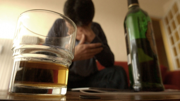 Mann mit Drink daheim.