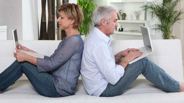Paar sitzend auf Sofa mit Laptop auf Knien.