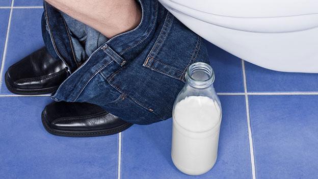Mann sitzt auf Toilette – neben ihm steht ein Joghurtdrink.