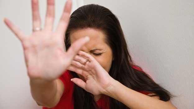 Eine Frau hält sich die Hand vors Gesicht.