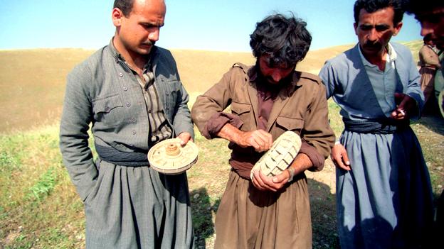 Drei Männer entschärfen eine Landmine.