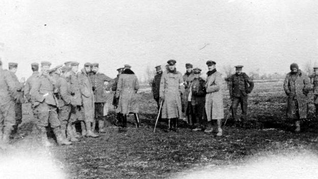 Sehr altes, unscharfes Schwarzweissbilod: Soldaten in langen Mänteln posieren zusammen.