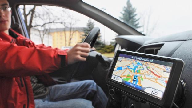 Jemand sitzt im Auto und lässt sich durch ein Navigationssystem helfen.
