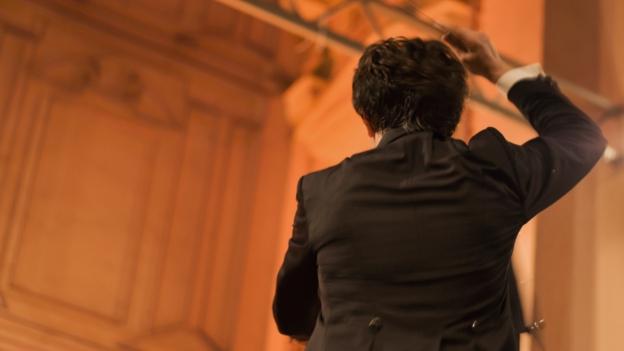 Ein Dirigent hebt die Hand.