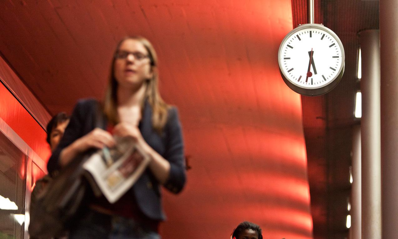 Eine Frau läuft vor einer Bahnhofsuhr, die halb sechs Uhr anzeigt.