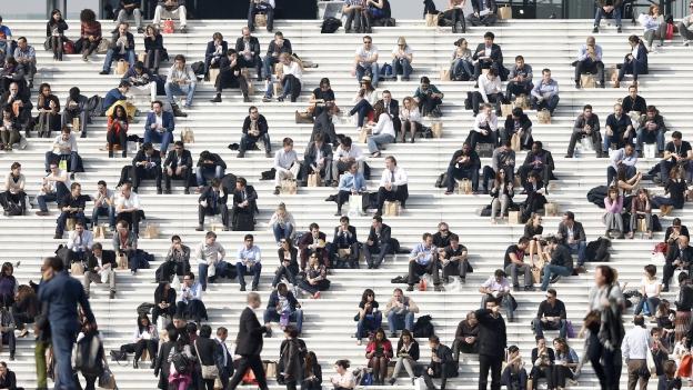 Viele Leute sitzten auf einer riesigen, breiten Treppe.