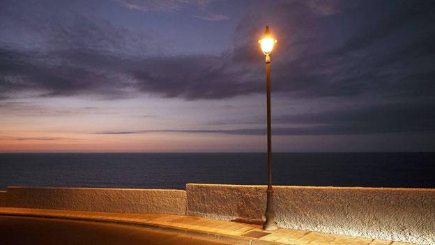 Eine leuchtende Strassenlaterne an der Meeresküste.