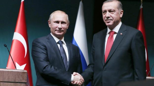 Zwei Männer in Anzügen schütteln sich die Hände.