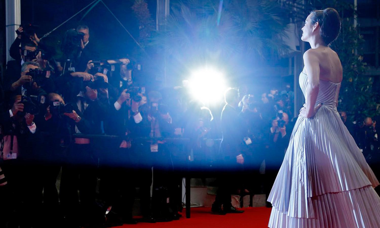Eine Frau in Abendkleid steht vor einem Blitzlichtgewitter.