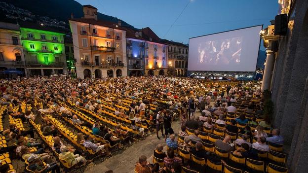 Festivalbesucher blicken auf die Leinwand auf der Piazza Grande