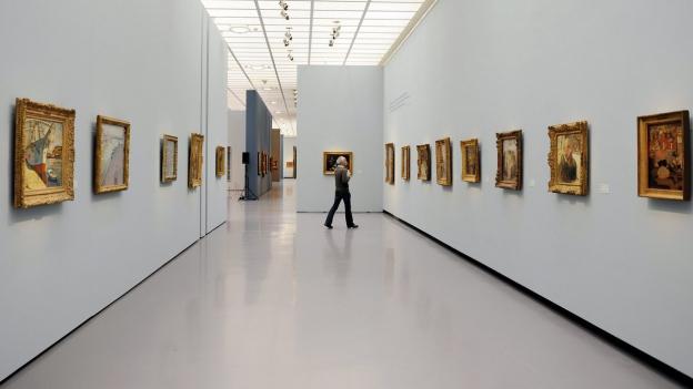 Rechts und links an der Wand je eine Reihe mit Bildern (in Goldrahmen).