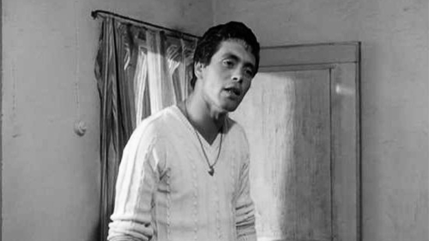 Schwarzweissbild: junger Mann in weissem Pullover.