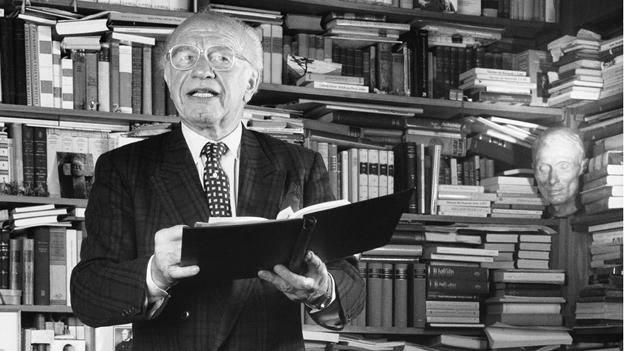 Gert Westphal vor einer Bücherwand und mit einem Buch in den Händen.