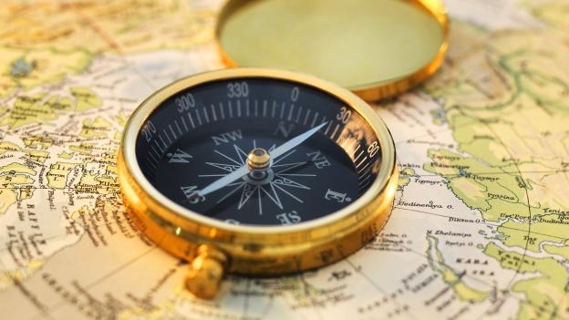 Foto eines goldenen Kompasses auf einer Landkarte