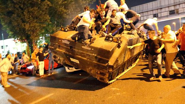 Demonstranten stürmen einen Panzer der Armee