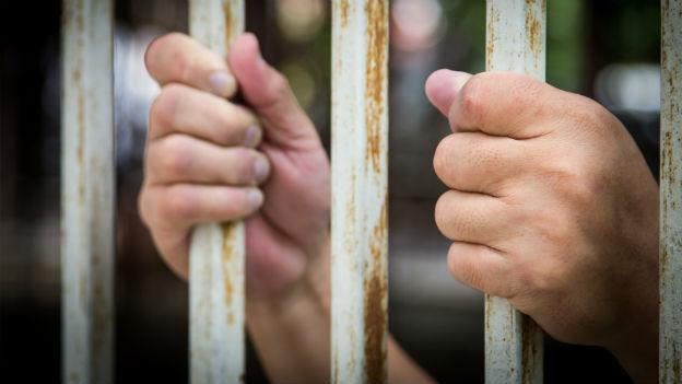 Hände hinter Gittern