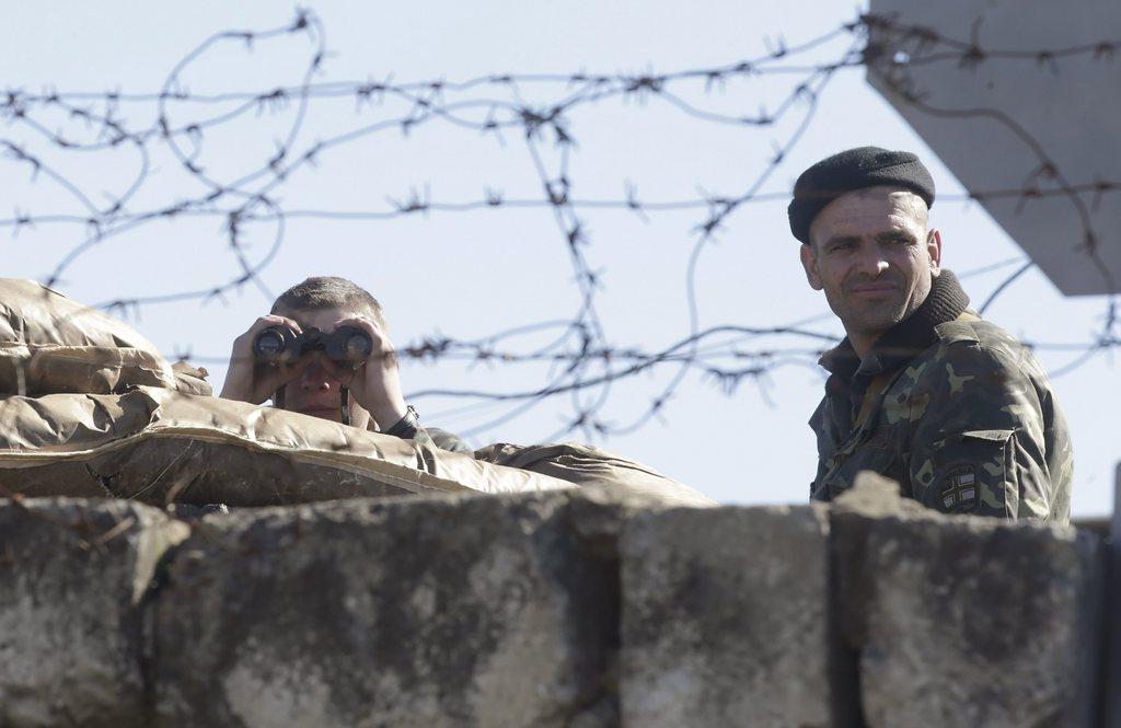 Ukrainische Soldaten auf einem Militärposten durch Stacheldraht fotografiert.