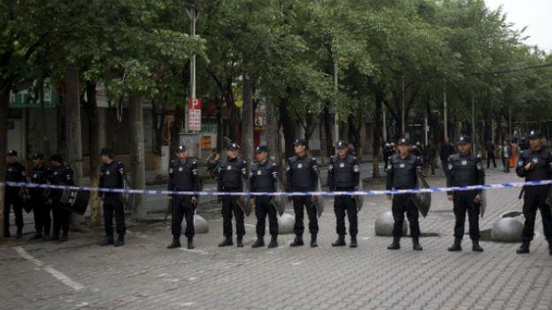 Mehrere Polizisten stehen vor einem Absperrband und bewachen einen Platz