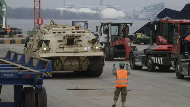 Lotse lenkt Panzer von einem Schiff (im Hintergund Meer).