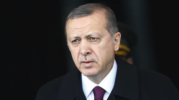 Portraitaufnahme des türkischen Staatspräsidenten Erdogan. Er trägt einen schwarzen Anzug, der hintergrund ist ebenfalls schwarz.
