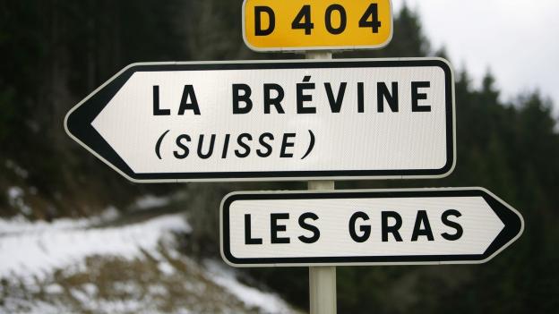 Wegweiser bei Les Gras, Frankreich, weist Richtung La Brevine im Schweizer Jura.