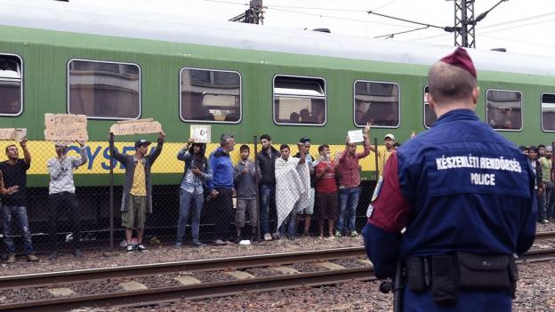 Flüchtlinge stehen vor einem Eisenbahnwagen, im Vordergrund ist ein ungarischer Polizist von hinten zu sehen.