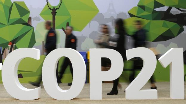 Das Logo des Klimagipfels, bestehend aus den Buchstaben «COP21», dahinter gehen Menschen vorbei.