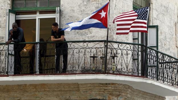 Eine alte Häuserfassade in Havanna, davor wehen eine kubanische und eine amerikanische Flagge.