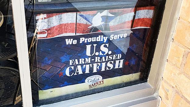 «We proudly serve U.S. farm-raised Catfish» steht am Fenster eines Fischrestaurants.