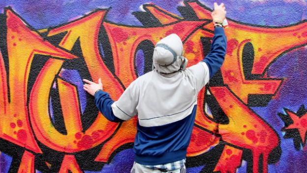 Ein Sprayer, den man nur von hinten sieht, sprayt ein Graffiti auf eine Wand.