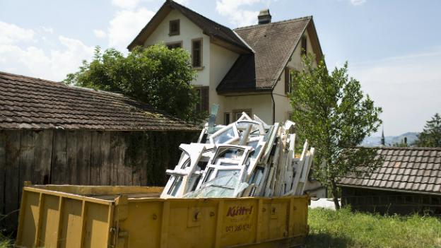 In einem Container liegen alte Fenster eines Hauses, die ersetzt wurden.