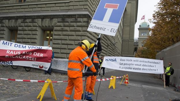 Initianten machen vor dem Bundeshaus mit Schildern auf die RASA-Initiative aufmerksam.