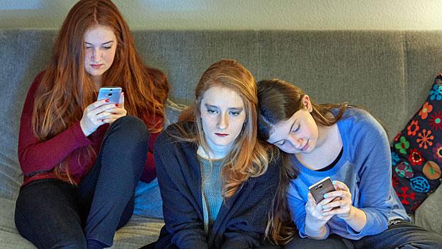 Drei junge Frauen auf einem Sofa konsultieren ihre Smartphones.