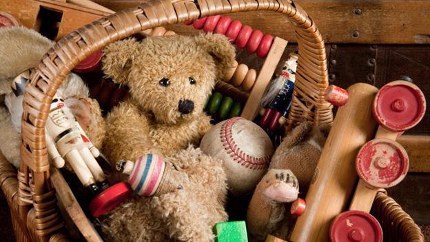 Ein Teddybär mit Knopfaugen sitzt inmitten von anderen Spielsachen in einem Korb.