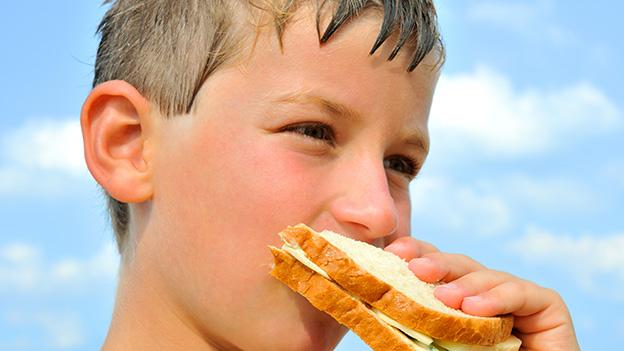 Ein Bub geniesst ein Sandwich mit Toasbrot und Käse.
