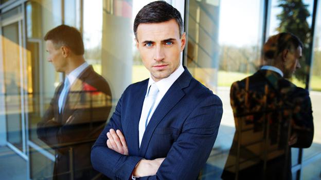Ein Mann im blauen Anzug spiegelt sich in der Glasfassade eines Gebäudes.