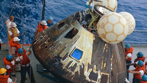 Männer in orangen Westen hieven die Landekapsel auf ein Schiff.