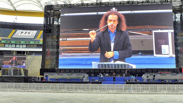 Ein Dirigent auf einer riesigen Leinwand in einem leeren Stadion.