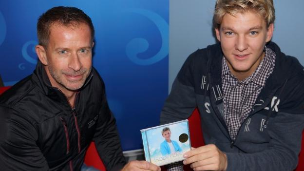 Robin Leon und Leonard auf roten Sesseln mit CD in der Hand.