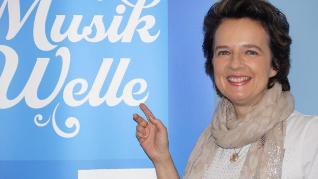Monika Martin im SRF Musikwelle Studio vor Banner.