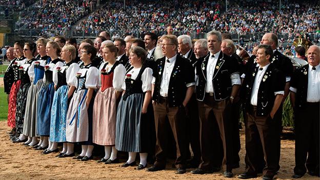 Eine Gruppe von Jodlerinnen und Jodlern in einer Schwingarena.