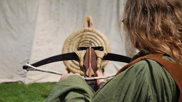 Ein Mann in mittelalterlicher Kleidung zielt mit einer Armbrust auf eine Zielscheibe, die aus einem Seil hergestellt wurde.