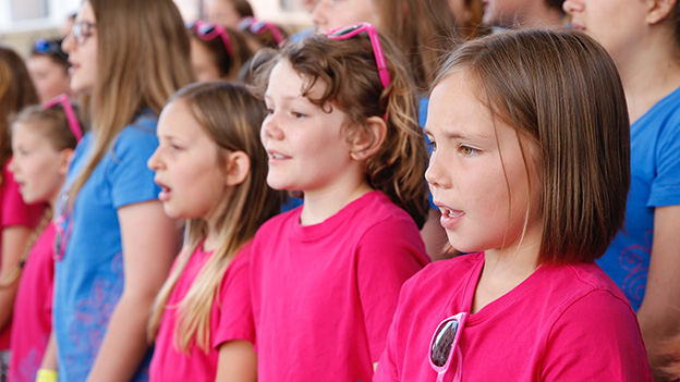Singende Kinder in bunten T-Shirts.