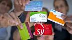Versicherte  präsentieren die Karten ihrer verschiedenen Krankenkassen.