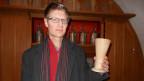 Martin Rüsch, Pfarrer am Zürcher Grossmünster, mit einem antiken Abendmahlwein-Becher, der schon 1776 im Einsatz war.