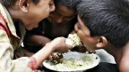 Drei Kinder teilen sich einen Teller Reis.