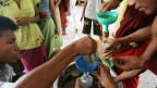 Zyklon-Opfer erhalten Gratis-Oel von lokalen Helfern.
