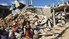 Palästinenser im Gazastreifen sitzen auf den Trümmern ihres Hauses.