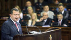 Vor leeren Kassen steht Premier Ivica Dacic, leere Taschen haben die SerbInnen.