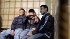 Drei ausländische Arbeiter, die anlässlich einer Raziia auf einem Moskauer Markt festgenommen wurden.